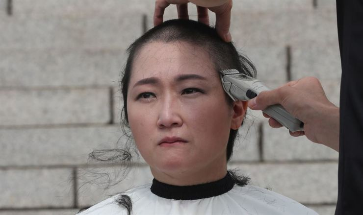 Lee Un-ju, an independent lawmaker, shaves her head at the National Assembly, Tuesday, in a symbolic protest calling for the withdrawal of the appointment of Cho Kuk as justice minister. Yonhap
