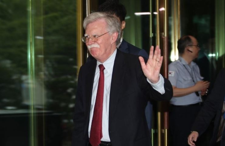 Former U.S. National Security Adviser John Bolton waves while leaving the headquarters of South Korea's Ministry of Foreign Affairs in Seoul on July 24. Yonhap