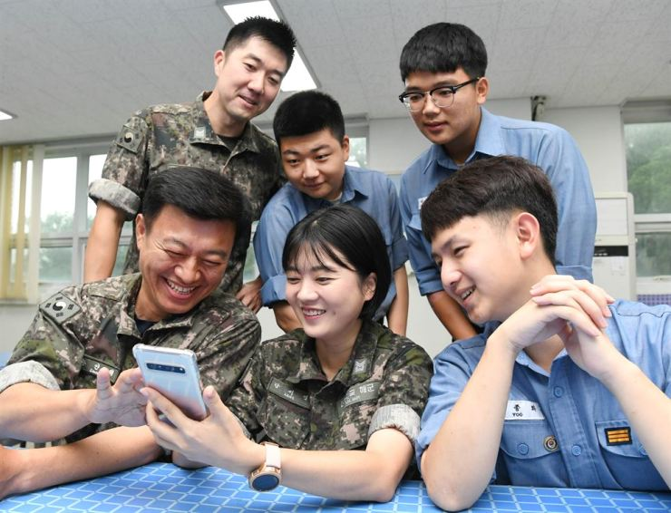 Kang Seo-yeon, center at the front, a chief petty officer of the Republic of Korea Navy, and her colleagues smile at a Navy base on Deokjeok Island, Incheon, as they look at a photo of Kang's four-year old son. Courtesy of Republic of Korea Navy
