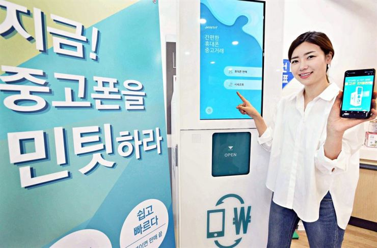 A model poses with a used phone buying machine installed at a Homeplus outlet in Gangseo-gu, Seoul, Wednesday. The machine checks the condition of used smartphones in three minutes and offers a buying price. If the seller accepts the deal, the machine takes the phone and transmits money into the seller's account. Machines were installed at 140 Homeplus outlets across Korea. Courtesy of Homeplus