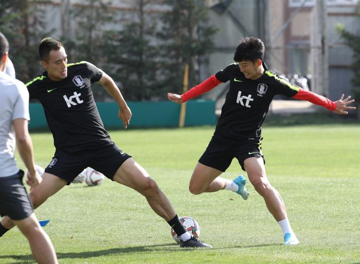 National football players Son Heung-min, right, and Kim Shin-wook in action during a training session in Istanbul Saturday, in preparation for their Qatar World Cup qualifying match against Turkmenistan, Tuesday. /Yonhap