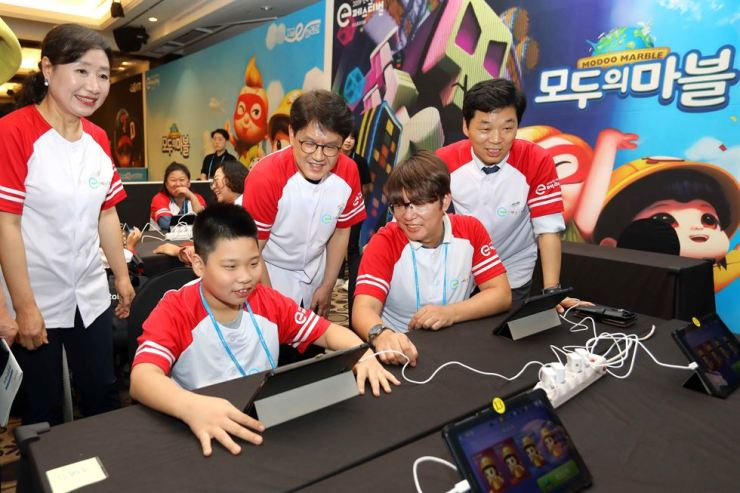 A student plays a mobile game, while Netmarble Cultural Foundation head Seo Jang-won, back row center, and other officials look on during the 2019 National e Festival Competitions for Students with Disabilities that kicked off at the K Hotel Seoul, Tuesday. The two-day event, co-hosted by Netmarble, aims to develop self-esteem and a sense of achievement in disabled students. / Courtesy of Netmarble
