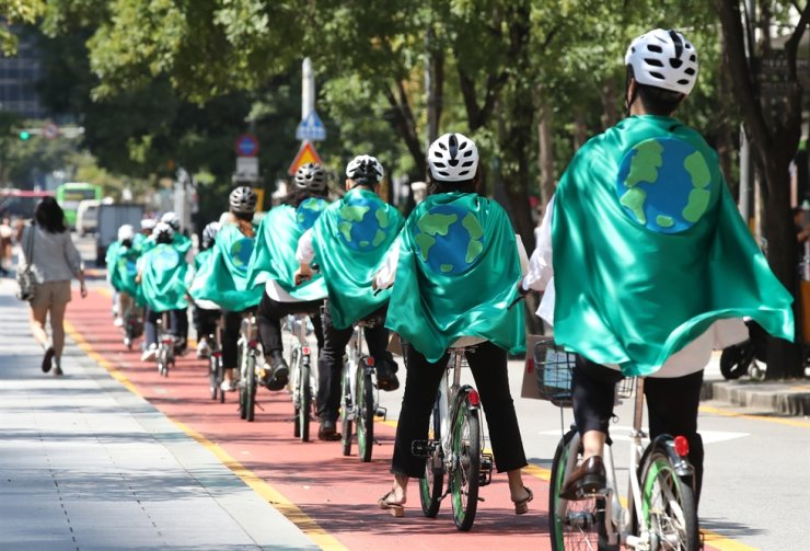Environmental activists in green capes bike along color-coded lanes for bikes next to cars by Cheonggye Stream in downtown Seoul, Sept. 18. / Yonhap