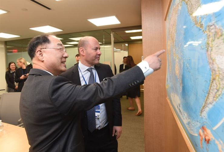 South Korean Finance Minister Hong Nam-ki, left, and Australian Treasurer Josh Frydenberg chat at the International Monetary Fund headquarters in Washington, the U.S., Oct. 19. Courtesy of the Ministry of Finance