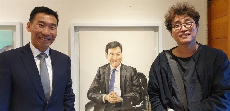 Australian Ambassador to Korea James Choi, left, and painter Lee Jae-yeol, stand beside Lee's portrait of Choi, Oct. 8. / Korea Times photo by Yi Whan-woo