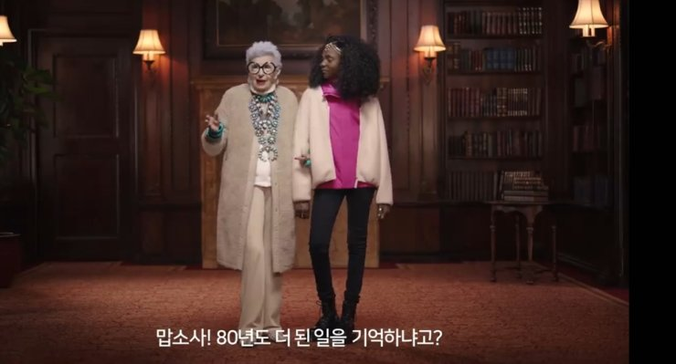 The advertisement shows an elderly fashion designer talking with a teenage fashion designer.