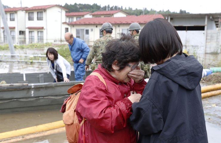 A woman cries in relief after being rescued from an area flooded by Typhoon Hagibis in Marumori, Miyagi prefecture, Japan, Oct. 14, 2019. Kyodo via Reuters