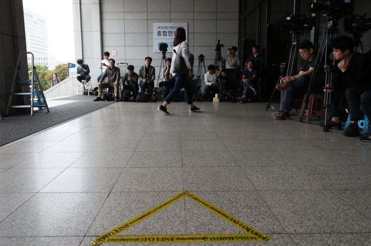 Photojournalists wait for Justice Minister Cho's wife at a photo line set up at the main entrance to the Seoul Central District Prosecutors' Office, Thursday. Prosecutors, however, brought Chung Kyung-shim in through a back door. / Yonhap