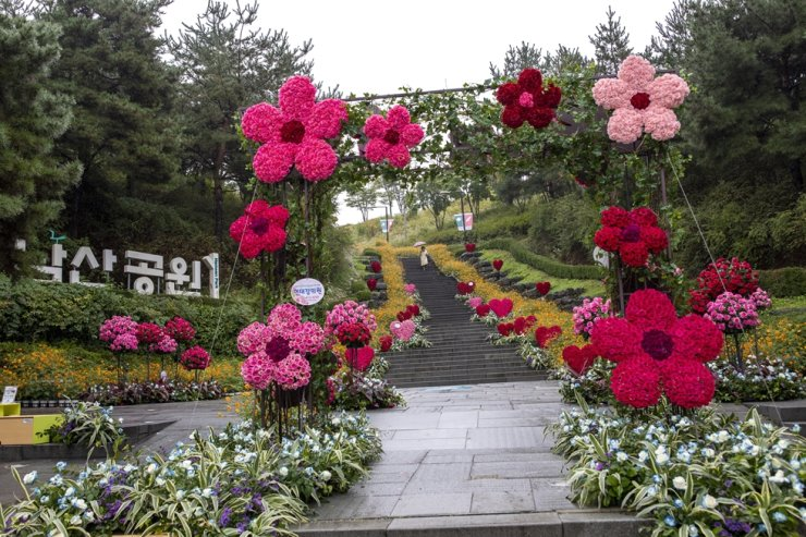 Floral decorations brave the rain at an entrance leading to Namsan Mountain Park in downtown Seoul, Monday. Up to 40 millimeters fell across the country, pulling the temperatures below 20C. The mercury is forecast to fall further on Tuesday, according to the Korea Meteorological Administration. Korea Times photo by Shim Hyun-chul