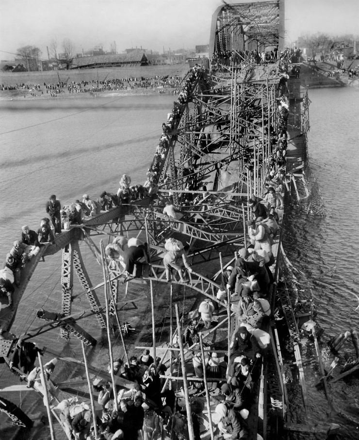 In this Dec. 4, 1950, file photo by former Associated Press photographer Max Desfor, residents from Pyongyang, North Korea, and refugees from other areas crawl perilously over shattered girders of the city's bridge, as they flee south across the Taedong River to escape the advance of Chinese Communist troops. AP-Yonhap