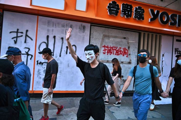 Graffiti is seen at the entrance of a fast food restaurant as people take part in a flash mob rally in the Mongkok district in Hong Kong on Oct. 5, 2019, a day after the city's leader outlawed face coverings at protests invoking colonial-era emergency powers not used for half a century. Pro-democracy protesters marched through Hong Kong in defiance of the ban on face masks as much of the city ground to a halt on Oct. 5 with the subway suspended and swathes of shops and malls shuttered following another night of violence. AFP