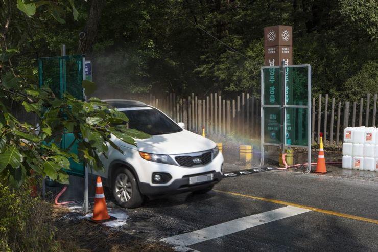 A car passes through a quarantine checkpoint in Korea National Arboretum in Pocheon, Gyeonggi Province, Tuesday. /Yonhap