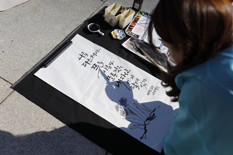 A woman participates in a hangeul writing competition at Gwanghwamun Square in central Seoul, Wednesday, Oct. 9 (Hangeul Day). Korea Times photo by Shim Hyun-chul
