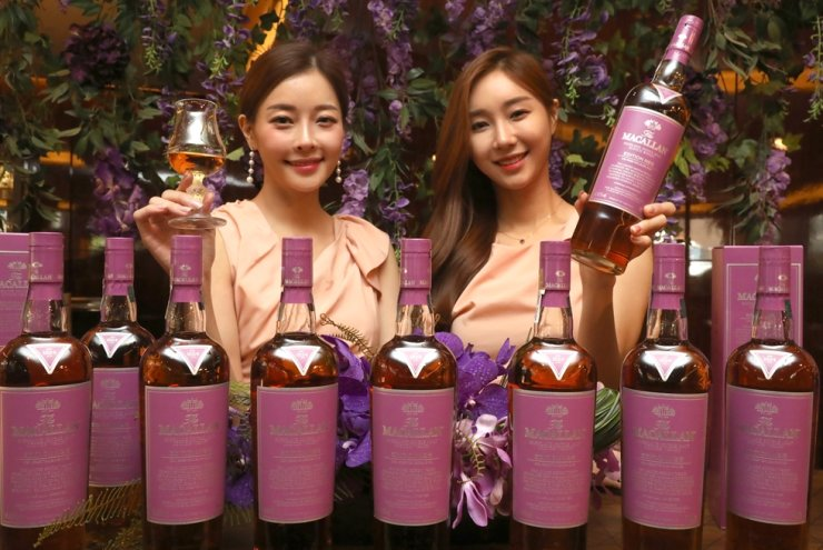 Models promote the Macallan Edition No.5 whisky at the Westin Chosun Hotel in downtown Seoul, Wednesday. The limited edition single-malt whisky is labeled with a special color, called the Macallan Edition Purple, developed by Pantone Color Institute. Yonhap