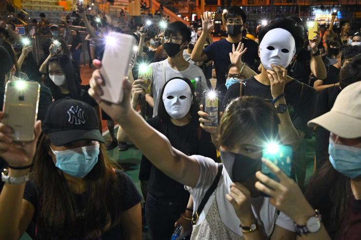 People wear masks and light up their mobile phones during a flash mob rally in the Sham Shui Po district in Hong Kong on Oct. 5, 2019. AFP