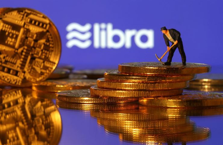 A small figurine stands on the representations of virtual currency in front of the Libra logo / Korea Times file