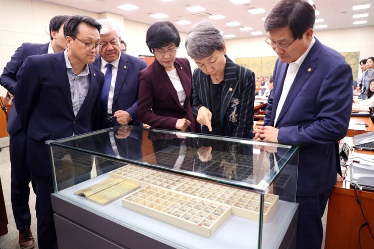Chung Jae-suk, second from right, chief of the Cultural Heritage Administration, and lawmakers look at 'Jeungdogaja,' a set of metal movable type, during a National Assembly audit of the culture agency, Monday. Yonhap