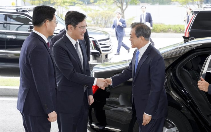 Lee Jae-yong, left, shakes President Moon Jae-in's hand during Moon's visit to a Samsung Display factory in Asan, South Chungcheong Province, Oct. 10. / Joint Press Corps