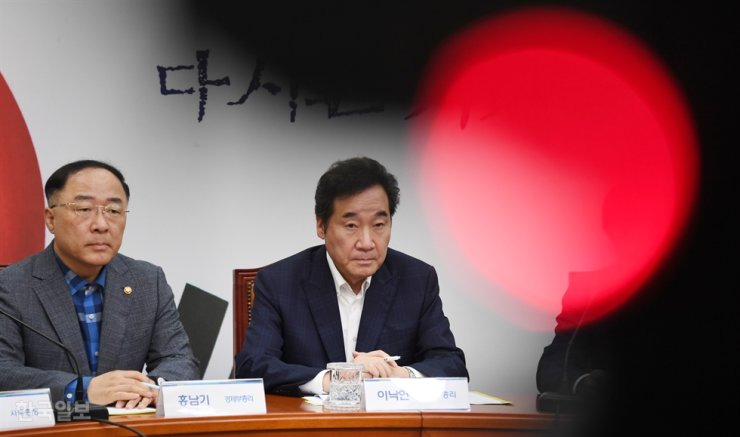 Prime Minister Lee Nak-yon, right, and Finance Minister Hong Nam-ki participate in a party meeting of the ruling Democratic Party of Korea at the National Assembly, in this Aug. 4 file photo. Korea Times file