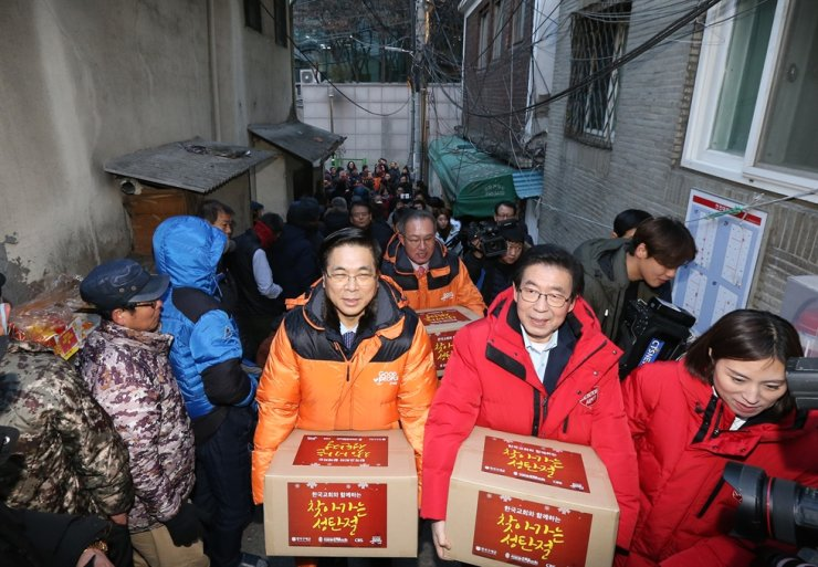 Yoido Full Gospel Church senior pastor Lee Young-hoon, left, and Seoul Mayor Park Won-soon carry boxes with daily necessities for people in need, in time for Christmas 2018./ Courtesy of Good People
