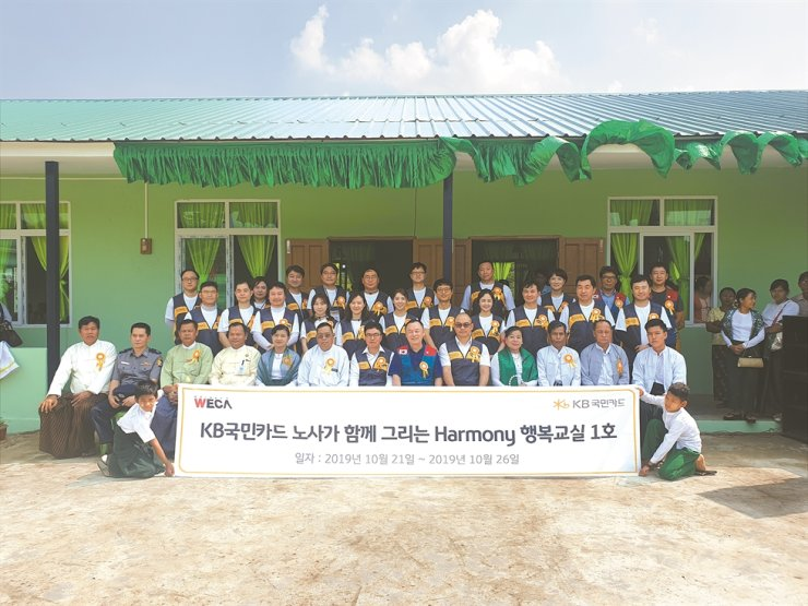 Members of KB Kookmin Card's management and labor pose after taking part in a week-long volunteer program held in Shwepyithar, in the outskirts of Yangon in Myanmar, Oct. 26. They refurbished school facilities and provided education materials to the schools. / Courtesy of KB Kookmin Card