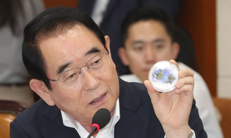 Rep. Park Myung-jae of the Liberty Korea Party displays a Dokdo commemorative coin, which is rumored to have been issued by the Bank of Tanzania in July, during the National Assembly audit of the Bank of Korea, Tuesday. / Yonhap