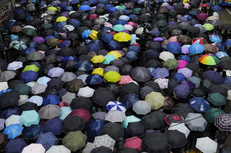In this Oct. 6, 2019, file photo, protesters march in the rain on a street in Hong Kong. Underground networks of volunteer medics have sprung up in Hong Kong to treat wounded protesters who fear arrest if they go to government hospitals. AP