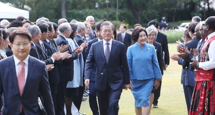 President Moon Jae-in, accompanied by first lady Kim Jung-sook, with Foreign Minister Kang Kyung-wha behind, is greeted by heads of foreign diplomatic missions, including ambassadors, during a reception at Cheong Wa Dae, Friday. Yonhap