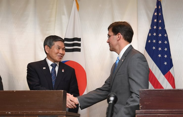 South Korean Defense Minister Jeong Kyeong-doo, left, and his United States counterpart, Mark Esper, shake hands after the end of a press conference at Avani+ Riverside Bangkok Hotel in Thailand, Sunday, which announced the countries will postpone their wintertime combined air exercises. Yonhap