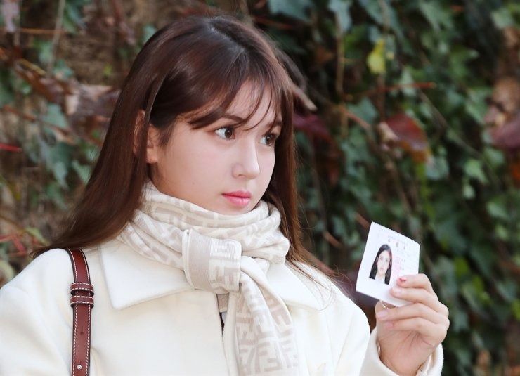 Jeon So-mi, former member of K-pop girl band I.O.I, poses for photos on Thursday morning before entering the examination site in Songpa-gu, Seoul. She is holding her test identification slip. Yonhap