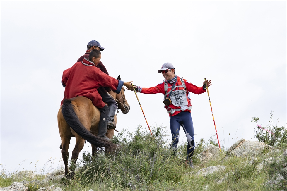 Ultramarathon runner Kim Gyeong-su, right, crosses a river while holding a rope at the 2019 Gobi March which began on July 28 and continued for seven days. Kim, a civil servant, has run a total of 6,300 kilometers in multiple desert marathons since 2003 when he first participated in an ultramarathon in the Sahara Desert. / Courtesy of Kim Gyeong-su
