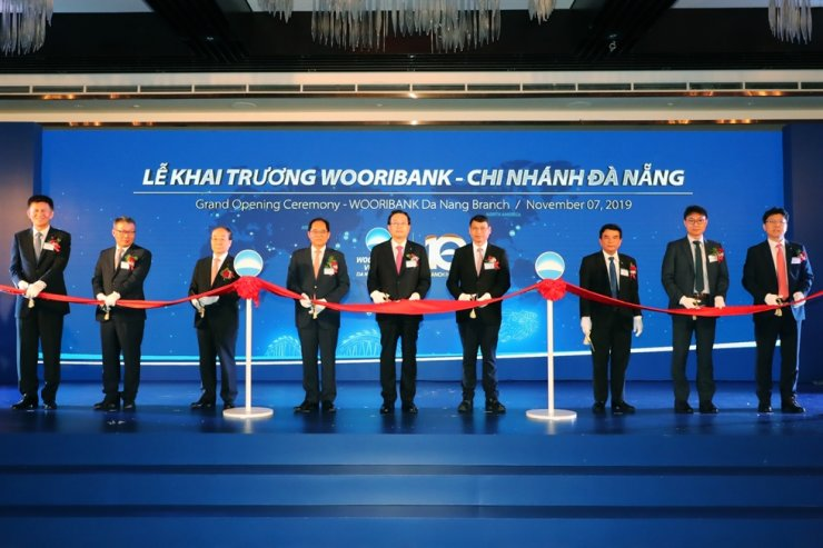 Woori Bank CEO Sohn Tae-seung, center, cuts a ribbon with officials from the bank and the Vietnamese government at an event celebrating the opening of its branch in Da Nang, Nov. 7.