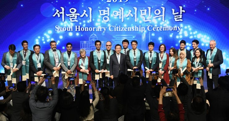 Seoul Mayor Park Won-soon, center, poses with 18 foreigners after giving them honorary citizenship of Seoul at the City Hall, central Seoul, Wednesday. Courtesy of Seoul Metropolitan Government