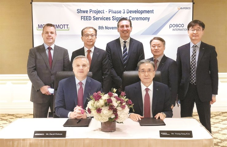 POSCO International CEO Kim Young-sang, seated right, and McDermott CEO David Dickson, seated left, pose after signing a contract in the U.S. Saturday (local time) on front-end engineering design services for the phase three development of POSCO International's Myanmar gas field project. Courtesy of POSCO International