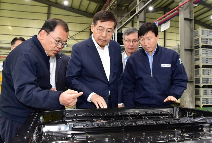 Shin Hak-cheol, center, vice chairman and CEO of LG Chem, inspects a battery pack case from Dongshin Motech in Haman, South Gyeongsang Province, Friday. / Courtesy of LG Chem