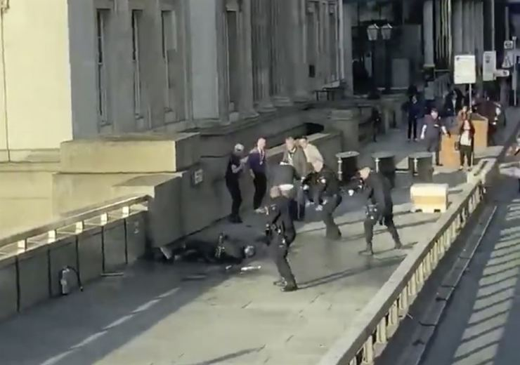 In this video grab made available by @HLOBlog, a man is surrounded by police after an incident on London Bridge, in London, Friday. AP-Yonhap