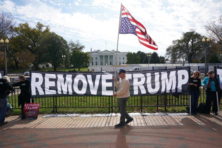 Activists hold a banner asking for the impeachment of US President Donald Trump on November 5, 2019 in front of the White House in Washington,DC. AFP