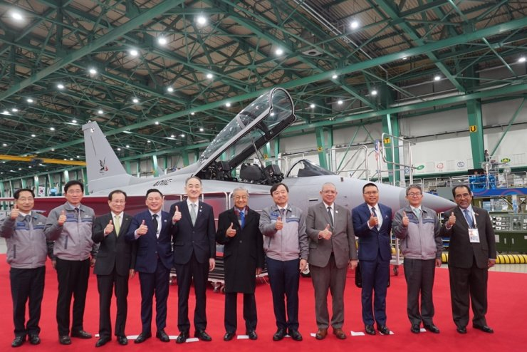 Malaysian Prime Minister Mahathir Mohamad, center, poses for a photo in front of South Korea's indigenous FA-50 fighter jet together with South Korean and Malaysian officials during his visit to the Korean Aerospace Industries (KAI) headquarters in Sacheon, South Gyeongsang Province, Monday. On his left is South Korea's Defense Acquisition Program Administration (DAPA) chief Wang Jung-hong and on his right, KAI CEO Ahn Hyun-ho. Courtesy of KAI