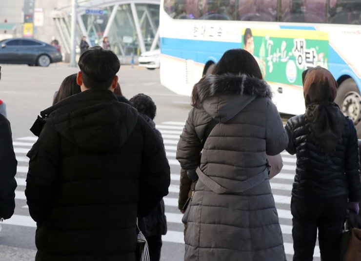 People bundle up on the street of Busan as cold temperatures hit Korea on Friday. Yonhap