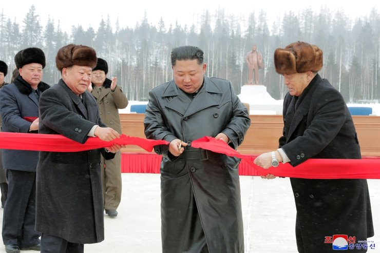 North Korean leader Kim Jong-un, center, cuts the tape during his attendance for the opening event marking the completion of the second-phase of a village modernization project in Samjiyon County, the city near Mount Peaktu, Dec.2, in this photo released by the country's state-run Korean Central News Agency (KCNA) the following day. KCNA-Yonhap