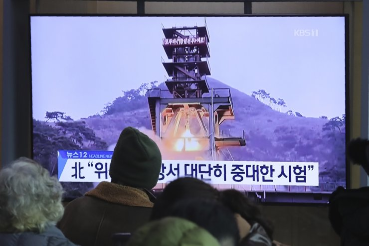 [PAP20191209098801848] People watch a TV screen showing a file image of a ground test of North Korea's rocket engine during a news program at the Seoul Railway Station in Seoul, South Korea, Monday. Yonhap