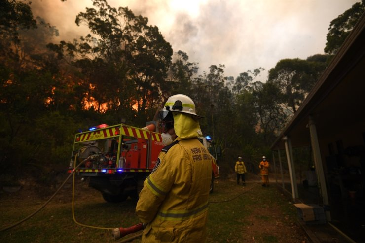 New South Wales (NSW) Rural Fire Service and Fire and Rescue NSW crews work to protect a property in Kulnura as the Three Mile fire approaches Mangrove Mountain, Australia, Dec. 6, 2019. EPA