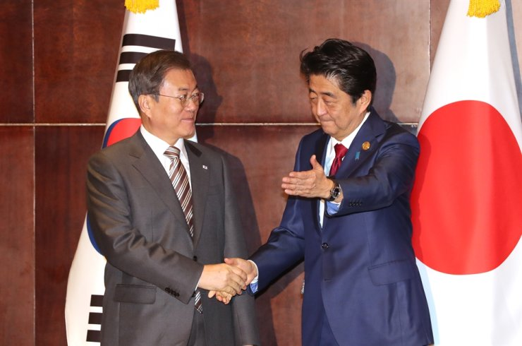 President Moon Jae-in, left, and Japanese Prime Minister Shinzo Abe shake hands before a summit in Chengdu, China, Tuesday. Yonhap