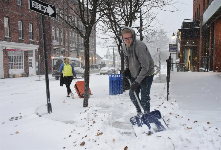 Zach Lusignan of Ryan's Landscaping shovels the snow on Spring Street in Williamstown, Mass. Sunday Dec., 1, 2019. AP