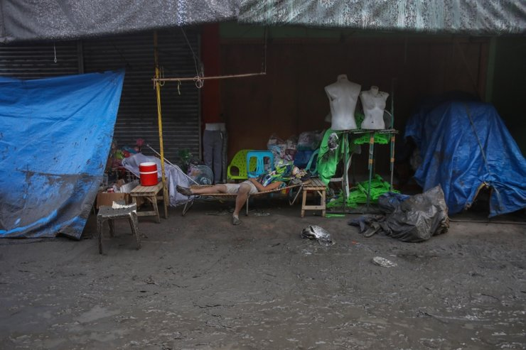 A man sleeps outside a store during a volcano eruption in Talisay, Batangas, Philippines, Jan. 13, 2020. Thousands of people have been ordered to evacuate as authorities in the Philippines raised the alert due to the increased activity of the Taal volcano, located in an island near Manila. EPA