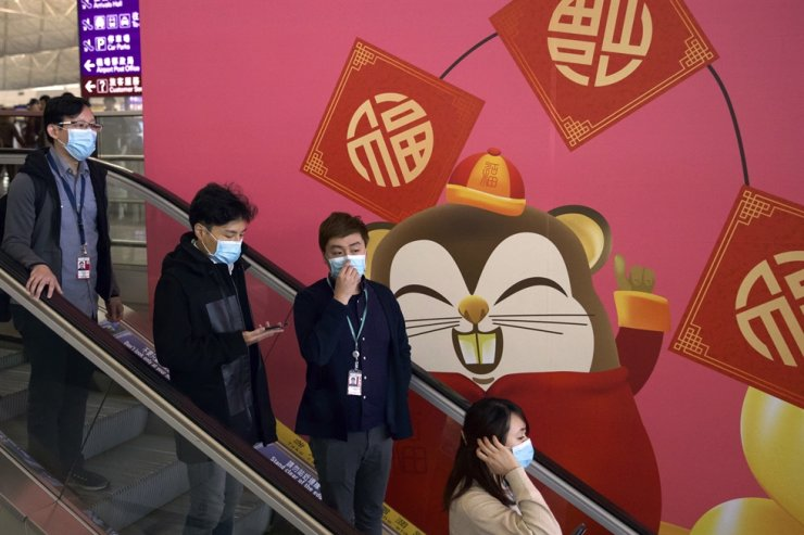 People wear face masks as they ride an escalator at the Hong Kong International Airport in Hong Kong, Tuesday, Jan. 21, 2020. Face masks sold out and temperature checks at airports and train stations became the new norm as China strove Tuesday to control the outbreak of a new coronavirus that has reached four other countries and territories and threatens to spread further during the Lunar New Year travel rush. AP