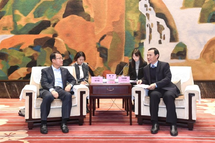 Celltrion Group Vice Chairman Gi Woo-seong, left, speaks with Ma Guoqiang, deputy party chief of Hubei Province, during a signing ceremony for Celltrion's investment for the building of a biomedicine plant in Wuhan, Hubei, on Jan. 20. Courtesy of Celltrion