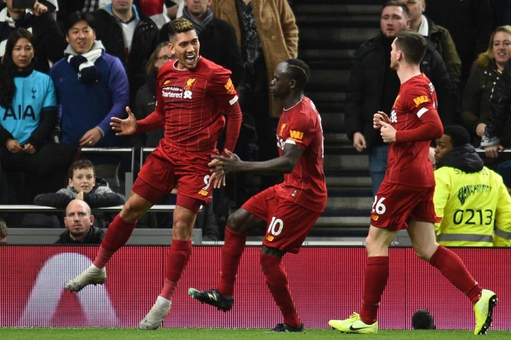 Liverpool's Brazilian forward Roberto Firmino, left, celebrates scoring the opening goal during the English Premier League football match between Tottenham Hotspur and Liverpool at Tottenham Hotspur Stadium in London, Saturday. / AFP-Yonhap
