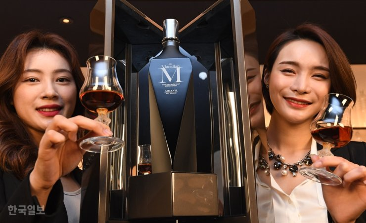 Models hold glasses of limited edition Macallan whisky during its launch at a hotel in central Seoul last March. / Korea Times photo by Bae Woo-han