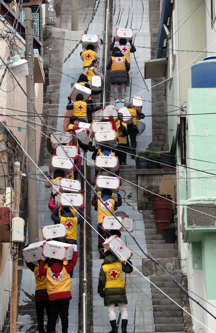 Volunteers from the Busan branch of the National Red Cross in the port city, walk up the stairs to deliver relief packages to impoverished households, Tuesday, ahead of